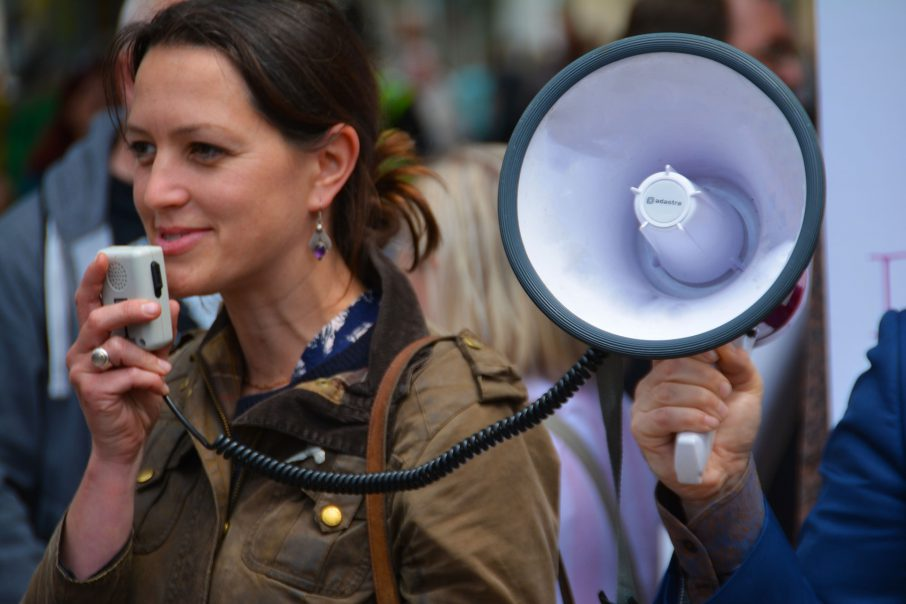 Girl speaking publicly into a megaphone about promotional pr